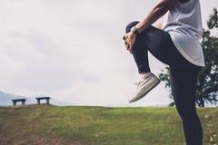 La donna dell'atleta che fa un certo allungamento esercita le gambe prima di runnin Fotografie Stock Libere da Diritti