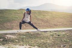 La donna dell'atleta che fa un certo allungamento esercita le gambe prima di runnin Fotografia Stock Libera da Diritti
