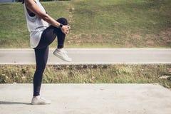 La donna dell'atleta che fa un certo allungamento esercita le gambe prima di runnin Fotografia Stock