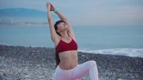 La donna dell'atleta sta pendendo indietro allungando le mani nella posa di yoga nella costa di mare video d archivio