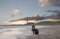 La donna dell'eleganza con la grande valigia cammina lungo la spiaggia vuota towar Immagine Stock