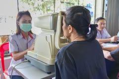La donna dell'occhio di prova dell'ottico con optometria automatica del rifrattometro Immagini Stock