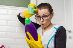 La donna della casalinga fa la pulizia con l'interesse che legge le istruzioni sul detersivo fotografie stock libere da diritti