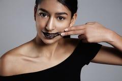 La donna della corsa mista di bellezza con un labbro sfrega il trattamento sopra Immagine Stock