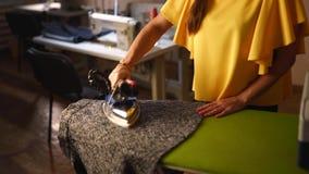 La donna della cucitrice cuoce a vapore il panno di lana del vestito ed utilizzare il ferro professionale nell'officina del sarto video d archivio