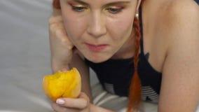 La donna della testarossa mangia la frutta fresca mentre si trova a letto movimento lento sano della prima colazione stock footage