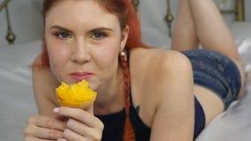 La donna della testarossa mangia la frutta fresca mentre si trova a letto movimento lento sano della prima colazione video d archivio