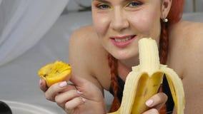 La donna della testarossa mangia la frutta fresca mentre si trova a letto movimento lento sano della prima colazione archivi video