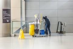 La donna delle pulizie con il suo carrello di pulizia pulisce il vetro di una st Immagini Stock