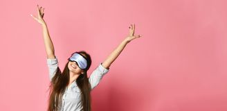 La donna dentro in una blusa e mette con una maschera per sonno su un isolamento rosa del fondo fotografie stock