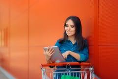 La donna di acquisto con la compressa del PC ed il carretto a mano vicino immagazzinano Immagine Stock Libera da Diritti