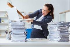 La donna di affari arrabbiata con la mazza da baseball in ufficio Immagine Stock