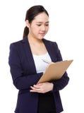 La donna di affari asiatica prende nota sulla lavagna per appunti immagini stock
