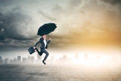 La donna di affari asiatica salta con l'ombrello immagine stock libera da diritti