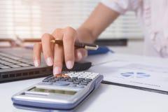 La donna di affari calcola circa costo e facendo l'ufficio di finanza a casa, i responsabili di finanza incaricano, affare di con immagini stock libere da diritti