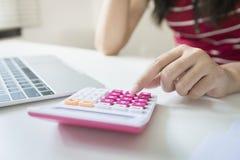 La donna di affari calcola circa costo e finanza fare all'ufficio Fotografia Stock Libera da Diritti