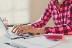 La donna di affari calcola circa costo e finanza fare all'ufficio immagine stock