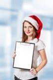 La donna di affari in cappello del Babbo Natale tiene i appunti Fotografia Stock