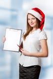 La donna di affari in cappello del Babbo Natale tiene i appunti Immagine Stock