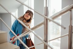 La donna di affari in cappotto aumenta le scale nel centro commerciale Acquisto Modo fotografia stock libera da diritti