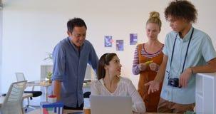 La donna di affari caucasica che lavora al suo computer portatile sta interagendo con altre gente di affari di 4k stock footage