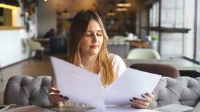 La donna di affari che ascolta la musica con le cuffie ed i documenti dei segni stock footage