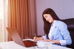 La donna di affari che lavora con il computer portatile e scrive un giornale Fotografia Stock