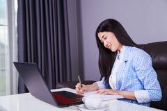 La donna di affari che lavora con il computer portatile e scrive un giornale Immagini Stock Libere da Diritti
