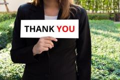 La donna di affari che mostra il segno bianco con vi ringrazia esprimere Fotografie Stock