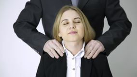 La donna di affari che parla su un telefono, impiegato massaggia le suoi spalle e collo dopo un lavoro lungo stock footage