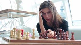 La donna di affari che pensa durante il gioco degli scacchi in ufficio ed ha emicrania, strategia archivi video
