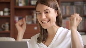La donna di affari che per mezzo del computer portatile a casa, buone notizie di ricezione femminili professionali ha eccitato so stock footage