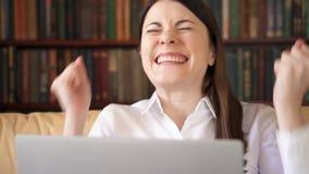 La donna di affari che per mezzo del computer portatile a casa, buone notizie di ricezione femminili professionali ha eccitato so video d archivio