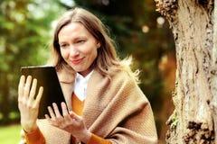 La donna di affari che per mezzo della compressa sopra irrompe l'autunno fotografia stock