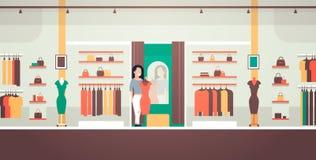 La donna di affari che prova sulla donna elegante del nuovo vestito che esamina i vestiti femminili del negozio di modo dello spe illustrazione vettoriale