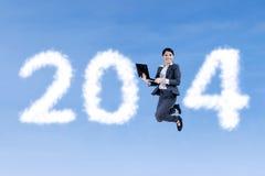 La donna di affari che salta sulle nuvole a forma di di 2014 Immagine Stock Libera da Diritti