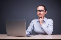 La donna di affari che si siede al suo scrittorio nel concetto di affari Fotografia Stock