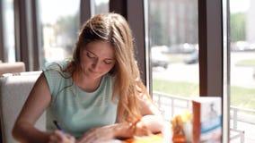 La donna di affari che si siede in caffè allo scrittorio compila un documento La ragazza scrive una penna a sfera archivi video