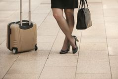 La donna di affari che sta con il viaggio insacca sul marciapiede della città Immagini Stock