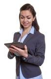 La donna di affari con capelli marroni ama il suo computer della compressa Fotografia Stock