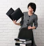 La donna di affari con la cartella, vestita in un vestito grigio posa davanti ad una parete bianca fotografie stock libere da diritti