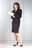 La donna di affari con i dispositivi di piegatura in mani fotografia stock