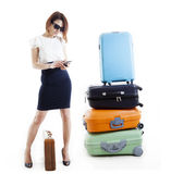 La donna di affari con i suoi suitcasas scrive i messaggi al cellulare immagini stock libere da diritti