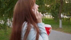 La donna di affari con i vetri in vestito leggero cammina nel caffè bevente del parco e nella conversazione su uno smartphone archivi video