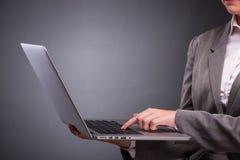La donna di affari con il computer portatile nel concetto di affari Fotografia Stock