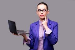La donna di affari con il computer portatile su fondo grigio Fotografie Stock Libere da Diritti