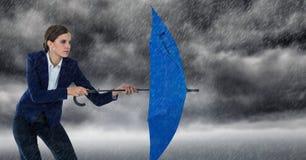 La donna di affari con l'ombrello e la didascalia piovono contro le nuvole di tempesta Immagini Stock
