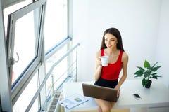 La donna di affari dell'ufficio lavora al computer Ufficio moderno leggero Vestito in maglione rosso e gonna nera Si siede sulla  Immagini Stock Libere da Diritti