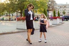 La donna di affari della madre prende il bambino alla scuola Immagine Stock