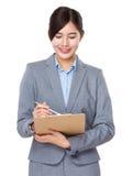 La donna di affari di Asain prende nota sulla lavagna per appunti fotografia stock